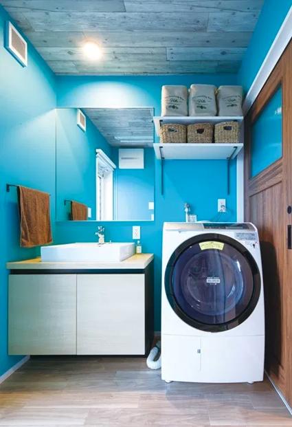大胆なピーコックブルーの壁面が、洗面室を異空間にしてくれます。ドラム式の洗濯機がまるで宇宙船のよう