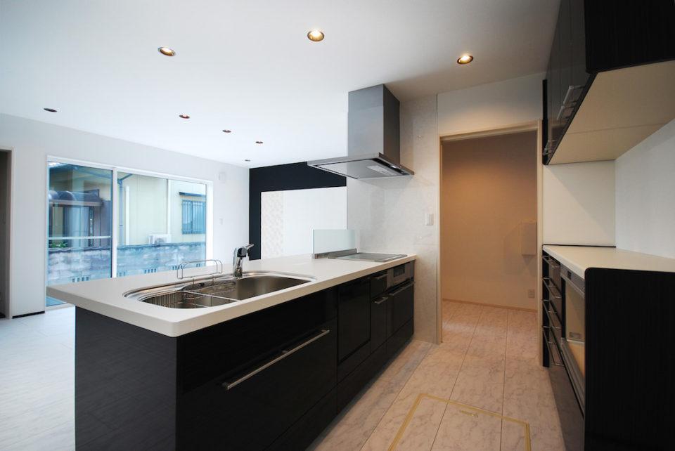 IHまわりの壁を無くした開放的なキッチン。白い天井に黒いフレームのダウンライトもこだわりのひとつ